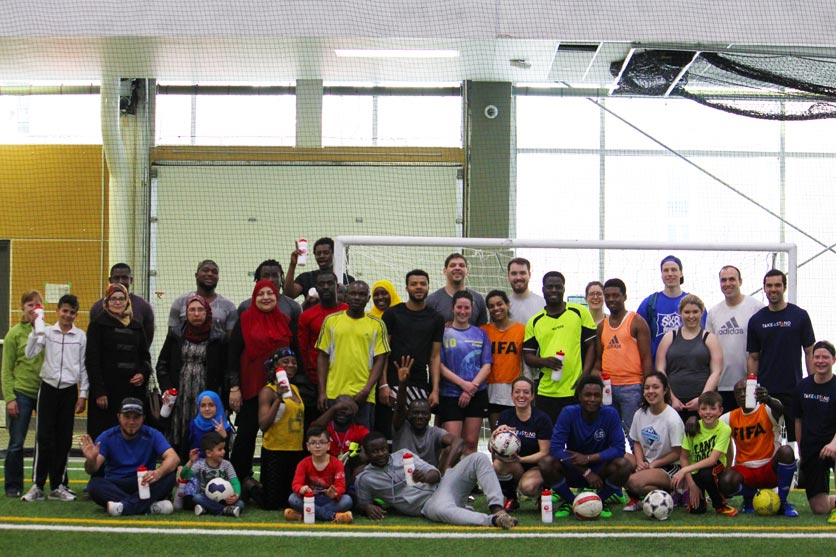 GenNext members from CWB National Leasing, PwC Canada and GenNext Winnipeg Council play soccer with refugees