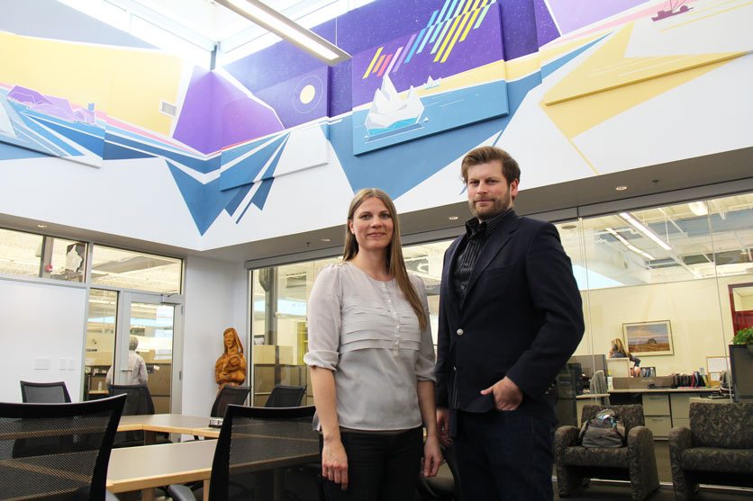 Peter Farmer (right) and Cherry Eidse, Facilities Coordinator, National Leasing  stand in front of Peter's mural in National Leasing's Canada Room.